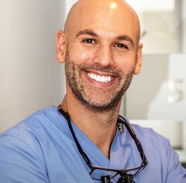 A headshot of Maroubra family dentist Dr Jamie Workman smiling with White teeth